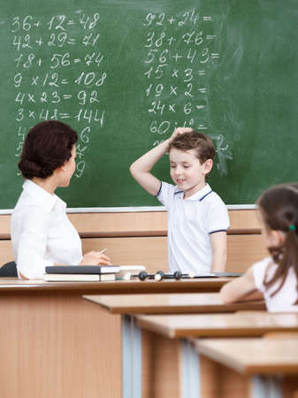 put up: Math teacher questions the pupil who doesnt know the answer Stock Photo