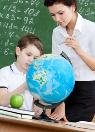 Geography teacher explains something to the pupil pointing at the globe photo