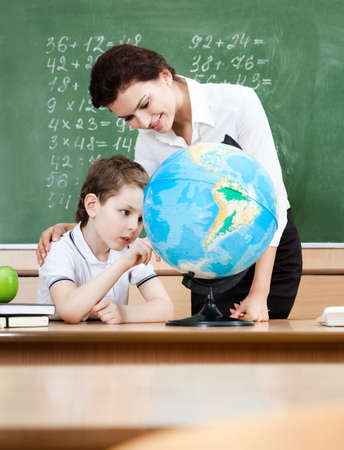 Little schoolboy studies geography with terrestrial globe photo