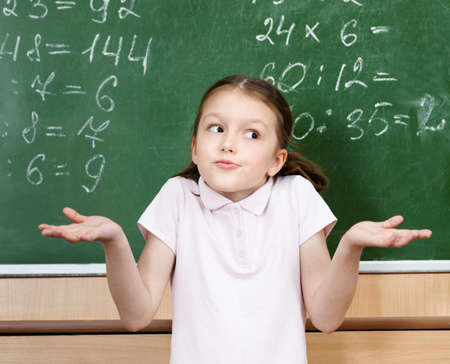 schoolhouse: Pupil doesnt know the right answer and spreads her arms Stock Photo
