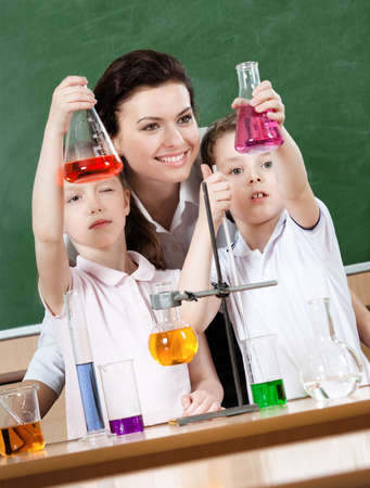 Little pupils study chemistry with their teacher photo