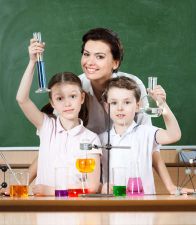 Little pupils study chemistry with their attractive school teacher photo