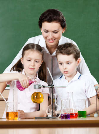 science lesson: Little pupils pour chemical liquids in different flasks while studying chemistry with their teacher