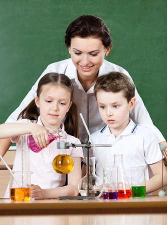 experimento: Los pequeños alumnos vierten líquidos químicos en diferentes frascos mientras se estudia la química con su profesor Foto de archivo
