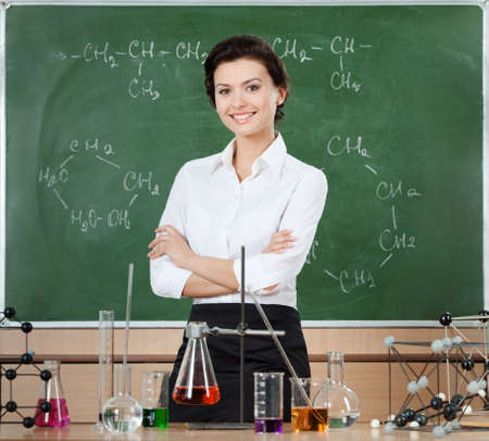 Smiley chemistry teacher surrounded with chemical glassware stands near the chalkboard photo