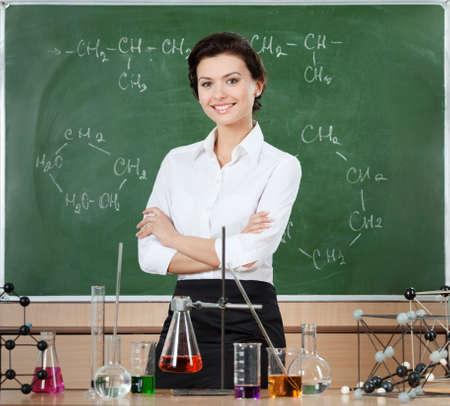 Smiley scheikundeleraar omringd met chemisch glaswerk staat in de buurt het bord