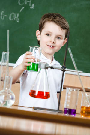 Little chemist shows colored liquid in conical flask at lab class Stock Photo - 14865723