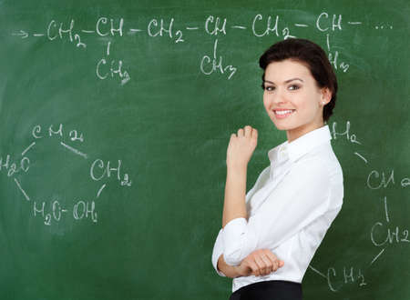 Smiley teacher hands chalk standing at the blackboard where the chemical formula is written photo