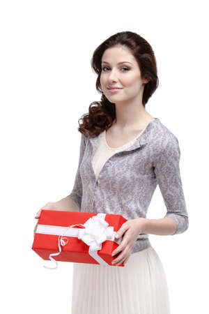 Young woman keeps a gift wrapped in red paper, isolated on white photo