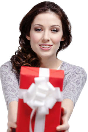 Young woman gives a gift wrapped in red paper, isolated on white photo