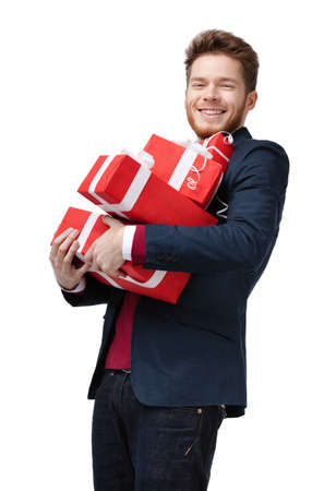 carries: Young man carries a lot of presents, isolated on white