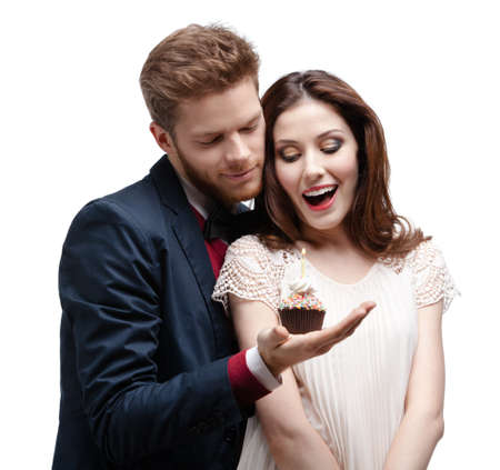 Man astonishes his wonderful girlfriend with birthday cake, isolated on white photo