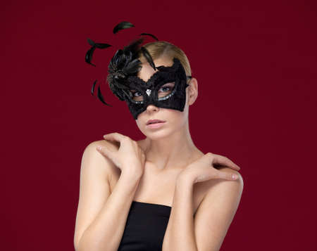 Attractive woman with black masquerade mask with feathers, isolated on purple photo