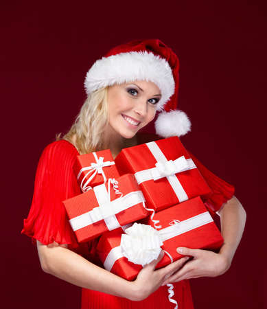 Beautiful lady in Christmas cap hands a set of presents, isolated on purple Stock Photo - 14980284