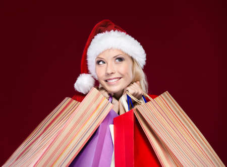 christmas shopping: Attractive woman in Christmas cap hands packets, isolated on purple