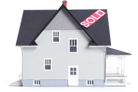 Real estate concept - home architectural model with Sold sign, isolated photo
