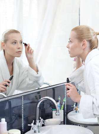 Woman mascaras her eyelashes in bathroom photo