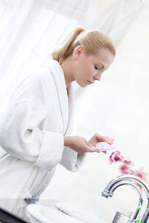 Wearing dressing gown lady washes face with lotion photo