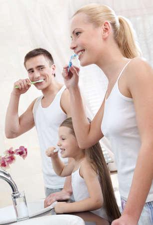 Happy family of three people brush their teeth in bathroom photo