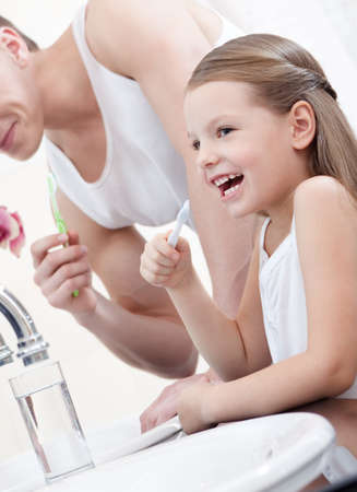 girl teeth: Little girl brushes her teeth with her father in bathroom Stock Photo