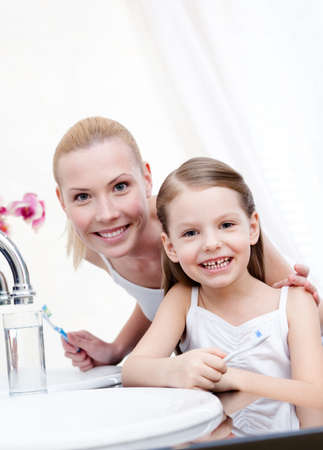 Little girl is ready to brush teeth with her mum photo
