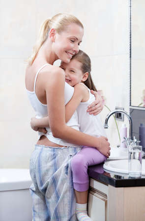fond of children: Mother and daughter embrace each other in bathroom. Trust relationship Stock Photo