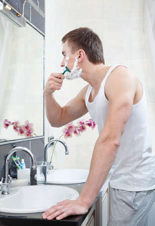 Muscular man shaves in the bathroom photo