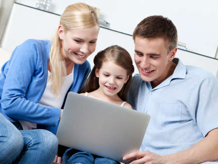 Happy family of three sit on the sofa with personal computer photo