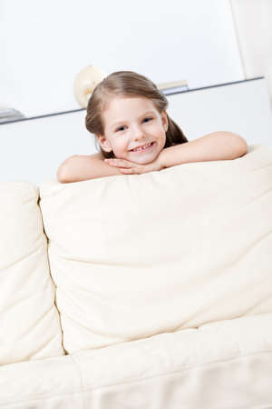 Little girl leans to the white leather sofa photo
