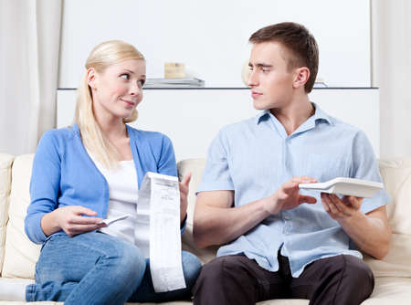 Husband and wife calculate the expenses sitting on the sofa photo