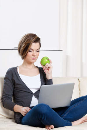 Sitting on the white leather sofa beautiful woman eats a green apple photo
