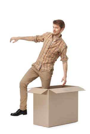 Young man gets out of the cardboard box, isolated, white background Stock Photo - 14980246