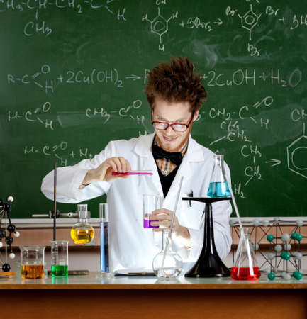 Mad professor pours some red liquid in beaker while making an experiment in his laboratory photo