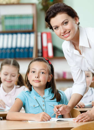 difficult task: Young teacher helps pupils to perform a difficult task Stock Photo