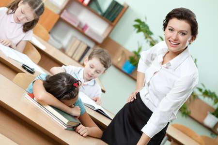 Tired schoolgirl sleeps at the school desk photo