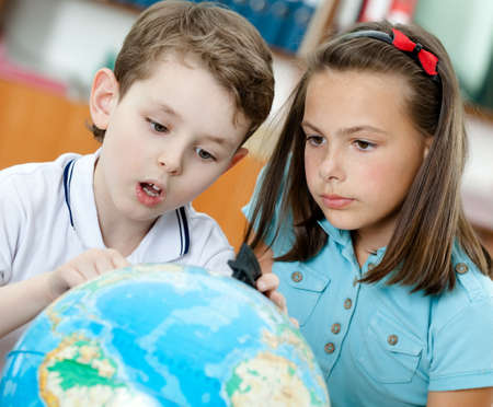 educational subject: Two friends amazingly look at the globe Stock Photo