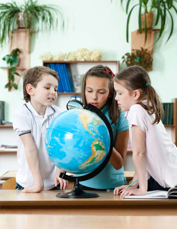 Friends stare at school globe and try to find something with magnifying glass photo