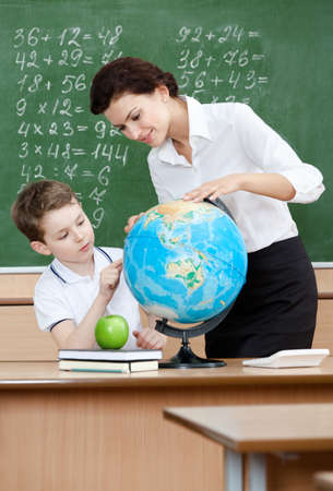 masters: Geography teacher shows something to the pupil at the terrestrial globe