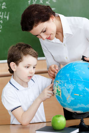 Little schoolboy studies geography photo
