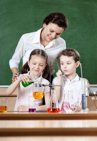 Little pupils study chemical liquids with their teacher photo