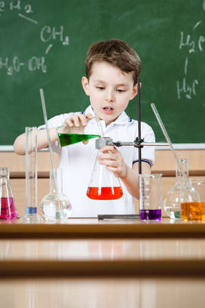 Little chemist holds scientific experiment photo