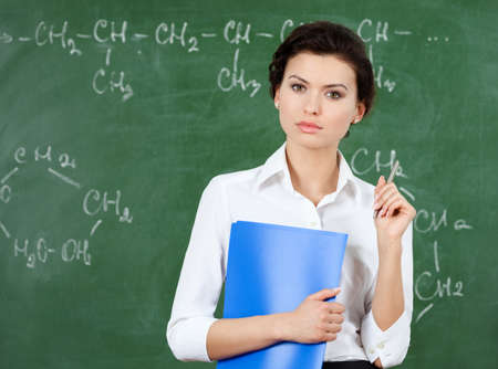 Serious teacher with folder stands at the blackboard photo