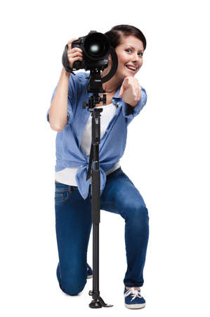 Woman makes pointing gesture while holding photographic camera, isolated on white photo