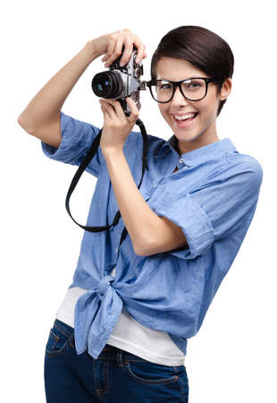 Beautiful girl in spectacles hands retro photographic camera, isolated on white Stock Photo - 14980371