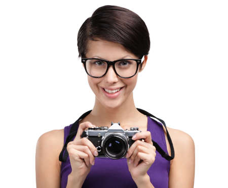 Pretty woman in spectacles hands retro photographic camera, isolated on white photo