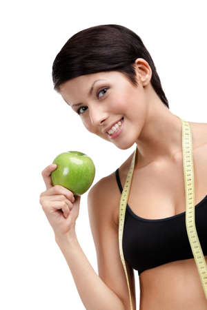 indulging: Indulging fitness woman with flexible ruler and green ripe apple, isolated on white