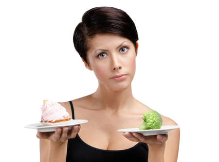 doubtfulness: Woman doubts between tasty tart and healthy cabbage, isolated on white