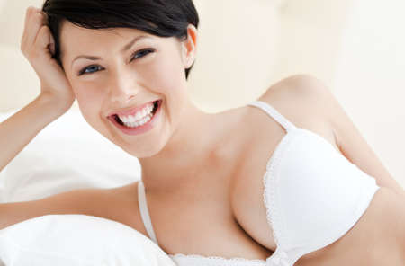 Woman in bra is lying in the comfortable bed photo