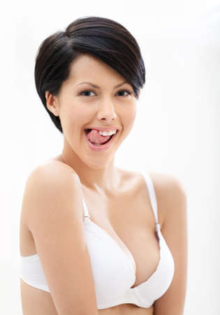 Portrait of woman in underwear putting out a tongue, isolated on white photo
