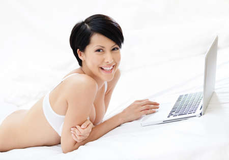 Woman in underwear is working on the pc while lying on the bed, isolated on white background photo